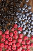 stock photo of blackberries  - raspberries and blackberry scattered on the wooden table - JPG