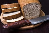 stock photo of whole-grain  - Whole grain brown bread on cutting board on black background - JPG