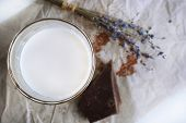 stock photo of bittersweet  - Glass of milk with chocolate chunks and dried flower on sheet of crumpled paper on white background - JPG