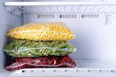 image of frozen  - Frozen berries and vegetables in bags in freezer close up - JPG