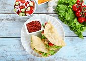 image of tacos  - Tasty taco with tomato dip on plate and vegetables on table close up - JPG