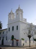 pic of asilah  - white stucco christian church in asilah in morocco showing bell tower and cross against blue sky - JPG