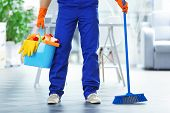 Young janitor holding cleaning products and tools in office poster