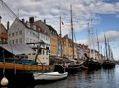 Nyhavn restaurant row as backdrop of the boat in Copenhaven's historic port. poster