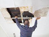 Man Repairing Collapsed Ceiling. poster