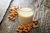 Heap of almonds and a glass of almond milk, on wooden surface poster
