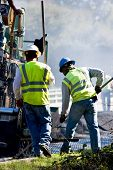 stock photo of work crew  - Two men working alongside an asphalt paving machine - JPG