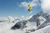 Skier jump in the mountains. Extreme ski sport. Freeride. poster