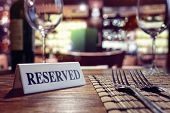 Restaurant reserved table sign with places setting and wine glasses ready for a party poster