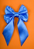 Blue satin bow on yellow velvet background