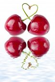 two cherries with tied into a heart love with reflection