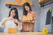 Two Young Asian People Startup Small Business Entrepreneur Sme Distrbution Warehouse With Parcel Mai poster