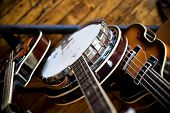stock photo of musical instruments  - Birdseye view of a mandolin banjo and bass sitting in a rack on a hardwood floor - JPG