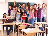 Estudante de grupo em sala de aula perto de quadro-negro.