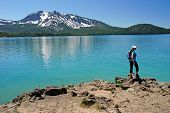 hiker gazing out across a turquoise mountain lake