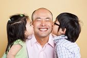A shot of an Asian father kissed by his kids