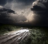 picture of ooze  - Muddy wet countryside road and dark storm clouds - JPG