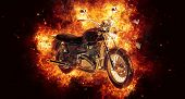 Dramatic burning motorcycle engulfed in fierce fiery orange flames and exploding sparks on a dark ba poster