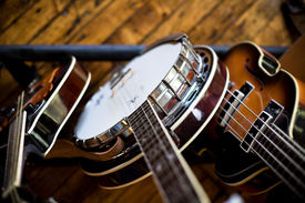picture of musical instrument string  - Birdseye view of a mandolin banjo and bass sitting in a rack on a hardwood floor - JPG