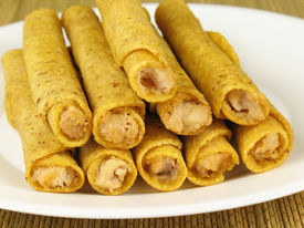 stock photo of flauta  - A plate of hot crispy chicken taquitos - JPG