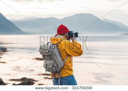 poster of Hipster Traveler Photographer Takes A Photo Beautiful Nordic Landscape On Professional Camera. Man T