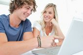 A couple smile as they sot together as the man looks at the screen and the woman looks at him