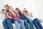 eine Gruppe von Freunden stützte sich auf die Seite wie sie Videospiele zusammen spielen.