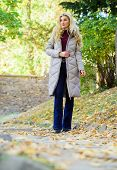 Jacket Everyone Should Have. Puffer Fashion Trend Concept. Girl Fashionable Blonde Walk In Autumn Pa poster