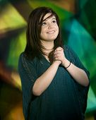 eine schöne junge Teenager nachschlagen, wie sie zum Herrn, bevor ein großes farbiges Kirchenfenster betet.