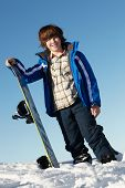 Young Boy With Snowboard On Ski Holiday In Mountains