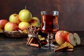 Glass Of Apple Juice Or Cider With Juicy Apples And Cinnamon Sticks On A Kitchen Table. poster