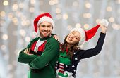 christmas, people and holidays concept - portrait of happy couple in santa hats at ugly sweater part poster