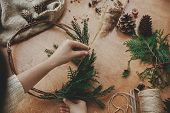 Christmas Wreath Workshop. Hands Holding Herbs, Fir Branches, Pine Cones, Berries, Thread, Scissors  poster