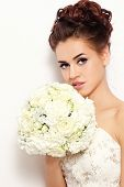 Beautiful bride with stylish make-up and hairdo holding bouquet in her hand, over white wall