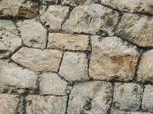 Stone Ancient Wall Paved With Cobble Stones, Closeup. Old Brown And Gray Cobblestone Wall Texture. N poster