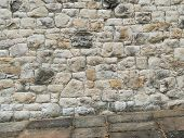 Ancient Stone Wall Paved With Cobblestone With Stone Pavement At An Angle. Stone Wall Building Featu poster