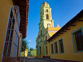 Old church sidelined by colorful houses in the colonial town of Trinidad in Cuba, a famous touristic landmark on the caribbean island