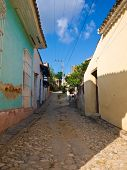 Narrow cobbled street in the colonial town of Trinidad in Cuba, a famous touristic landmark on the caribbean island poster