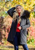 Girl In Warm Coat Stand In Park Nature Background Defocused. Woman Long Blonde Hair Wear Stylish Out poster