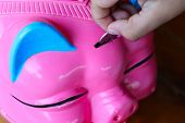 Pink Piggy Bank For Coin And Banknote Savings. Hand Inserting A Coin For Savings In A Box. Financial poster