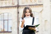 Keep Writing. Happy Little Girl With Textbook And Writing Pen Outdoor. Small School Child Practising poster