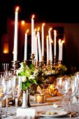 a large wedding table set for fine dining with lots of candles