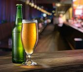 Glass of light beer and green beer bottle on the bar counter. Behind blurred background. poster