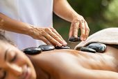 Closeup of masseuse hands placing hot stones on woman back at resort. Masseuse massaging body at spa poster