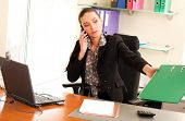Business woman sitting in the office in front of the laptop and calling by cell phone