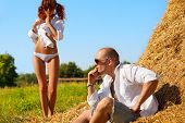 Erotic scene between brooding man lieing on hayloft and his lovely girl