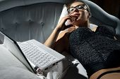 stock photo of masturbate  - Portrait of woman lying on bed with a laptop and play with herself - JPG