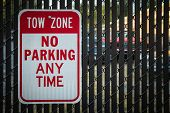 Tow Zone No Parking Sign On Black Fence Warns People Away From Parking Lot poster