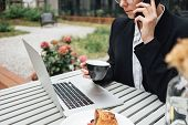 Beautiful Business Woman Sitting On Veranda At Cafe While Working On Laptop And Talking On Smartphon poster