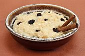 Large Bowl Of Creamy Rice Pudding With Raisins And Cinnaomon Sticks.